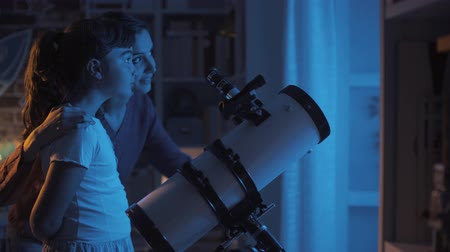 bámul : Happy young sisters watching stars with a telescope at night, astronomy and leisure concept