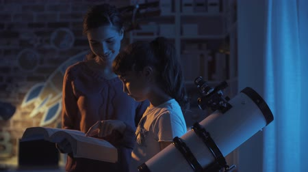csillagászati : Young happy sisters watching TV at night with studying astronomy books, learning and leisure concept