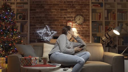 christmas tree with lights : Sad woman having a Christmas present at home on a sofa