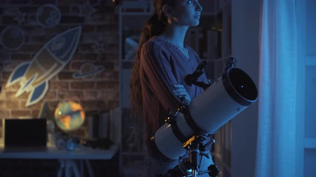 csillagászati : Young woman watching stars using a telescope, she is looking away, astronomy and science concept