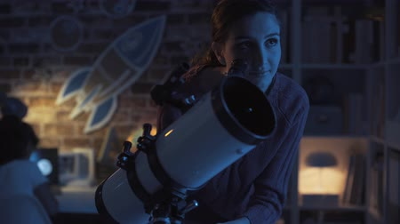 teleskop : Young smiling woman watching stars at night using a professional telescope, astronomy and science concept Stok Video