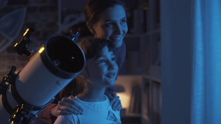 времяпровождение : Happy young girls stargazing with a telescope, they are learning astronomy together at home