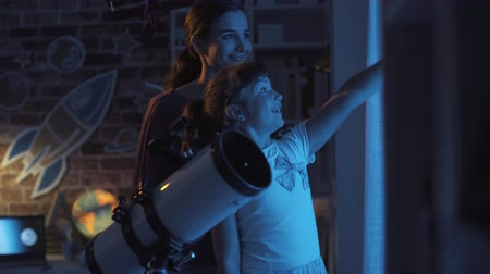 teleskop : Cheerful girls watching stars and learning astronomy together, science and discovery concept Stok Video