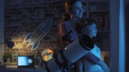 csillagászati : Loving sisters stargazing together at night with a professional telescope and hugging, imagination and science concept Stock mozgókép