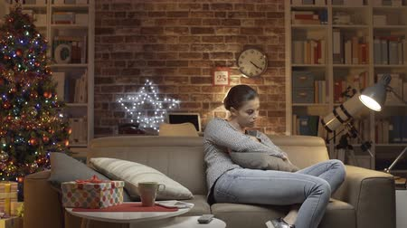 ümitsizlik : Sad woman having a Christmas Eve at home on a sofa Stok Video