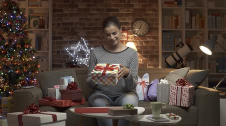 abundância : Joyful woman receiving a lot of Christmas presents at home, she is shaking a box and making a gift