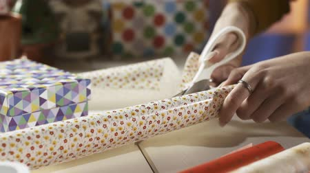 inpakpapier : Woman cutting wrapping paper with scissors and preparing Christmas gifts at home