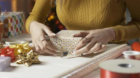 tilt : Young woman preparing Christmas gifts at home, she is folding wrapping paper, holidays and celebration concept Stock Footage