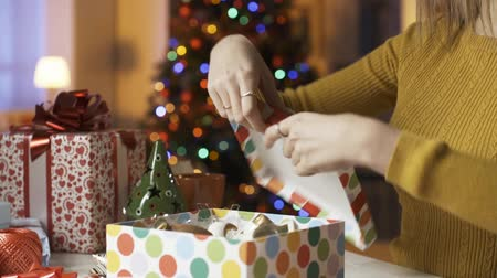 hediyeler : Smiling young woman preparing a present at home, she is closing a gift box, Christmas tree with lights in the background Stok Video