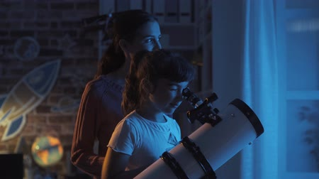 csillagászati : Sisters stargazing together and learning astronomy, the older girl is setting the telescope Stock mozgókép