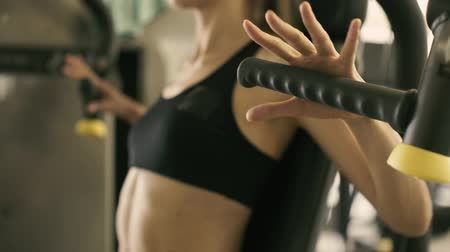 contra : Young athletic woman walking in the gym and having her fitness workout routine with exercise machines, hands close up, sports and motivation concept, video montage Stock Footage