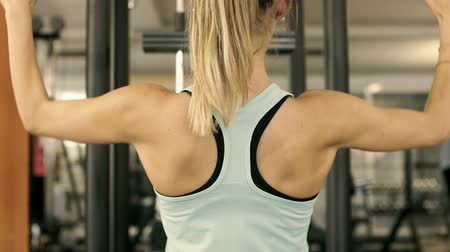 contra : Fit young woman working out on a lat pull down machine at the gym, video montage Stock Footage