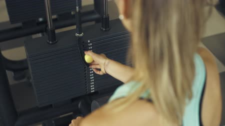 kilogram : Young athletic woman working out at the gym, she is setting weight on an exercise machine