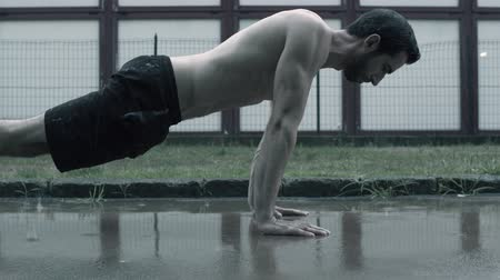Confident brave athlete performing push-ups under the rain on the street