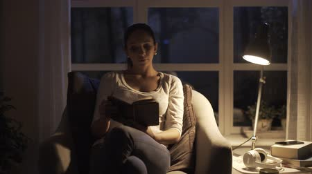 Young woman reading a book at home at night, she hears a noise outside and gets scared