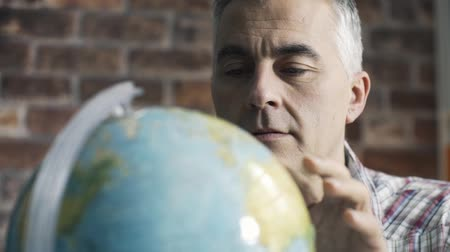 Man searching for places and locations on globe, he is planning to travel