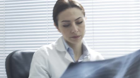 Professional female doctor working at desk, looking at patients radiograph and typing on the laptop