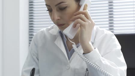 телефон доверия : Professional female doctor giving a consultation on the phone, she is talking and holding the receiver