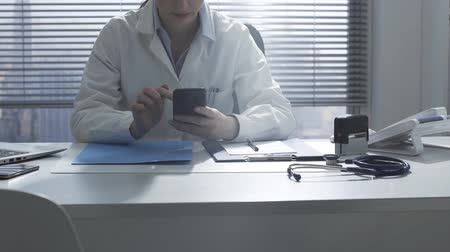 Professional female doctor working in an office, using medical apps on her smartphone, healthcare and technology concept Стоковые видеозаписи
