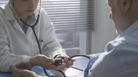 hypertension : Professional female doctor sitting at office desk and measuring blood pressure of a patient, healthcare and prevention concept Stock Footage