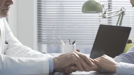 expressing negativity : Caring friendly doctor holding patients hands and supporting her, she received a bad diagnosis and feels sad Stock Footage