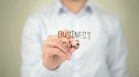 idiom : Business Goals, Man writing on transparent screen Stock Footage