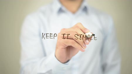 idiom : Keep it Simple, Man writing on transparent screen