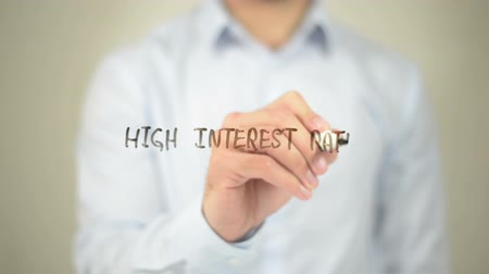 boletim : High Interest Rates, Man writing on transparent screen Stock Footage