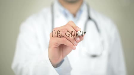 tesisler : Pregnant, Doctor writing on transparent screen Stok Video