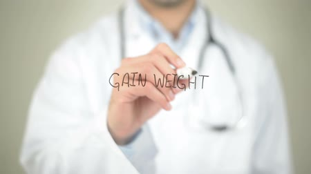 com escamas : Gain Weight, Doctor writing on transparent screen Stock Footage