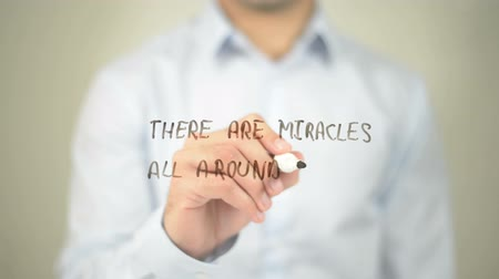 addiction recovery : There Are Miracles All Around you, man writing on transparent screen