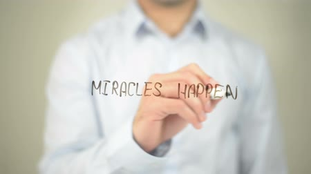 addiction recovery : Miracels Happen , man writing on transparent screen