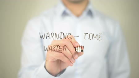 waster : Warning - Time waster Ahead, man writing on transparent screen