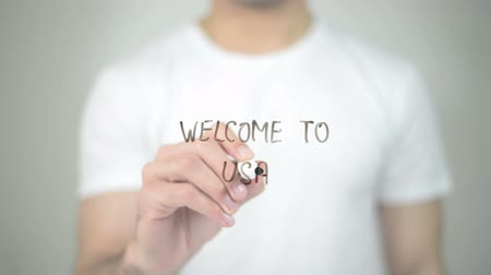 asal : Welcome to USA, man writing on transparent screen Stok Video