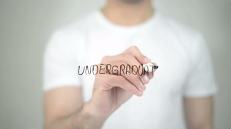 tradição : Undergraduate, man writing on transparent screen Stock Footage