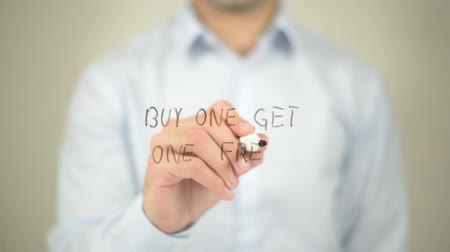 promover : Buy One Get One Free , man writing on transparent screen Stock Footage