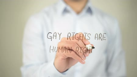 haklar : Gay Rights Are Human Rights , man writing on transparent screen Stok Video
