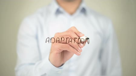 adapt : Adaptation, man writing on transparent screen Stock Footage