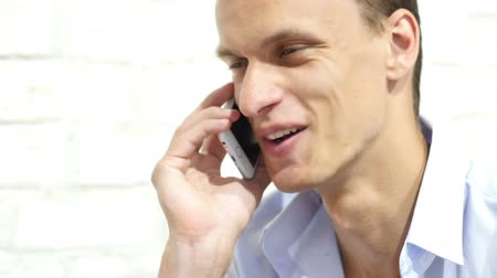 czytanie : Close up of young smiling businessman talking on smartphone