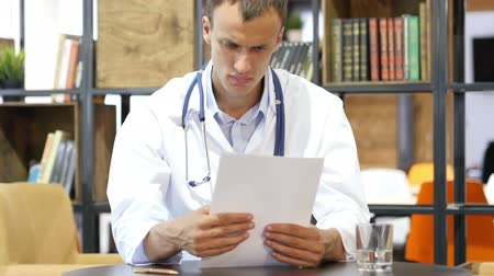 przychodnia : Medical office - male doctor looking down reading documents thinking Wideo