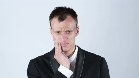 зубы : Toothache. Frustrated young man touching his cheek , white background