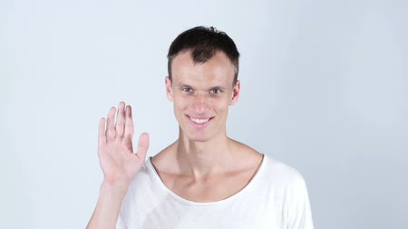хорошее здоровье : portrait of smiling man standing and showing hand sign of hi and bye bye Стоковые видеозаписи