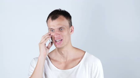 cancellation : Angry handsome man getting bad news on the phone Stock Footage
