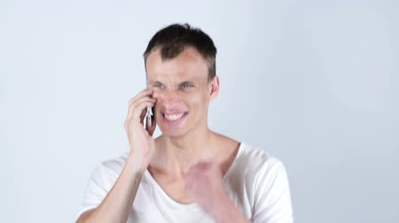 мобильный телефон : Portrait of a handsome young business man on cell phone getting good news Стоковые видеозаписи