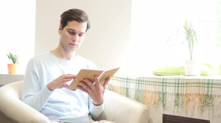 kahve molası : Young man is sitting on a sofa and reading a book
