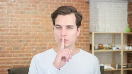 urge : young man silent quiet gesture with finger