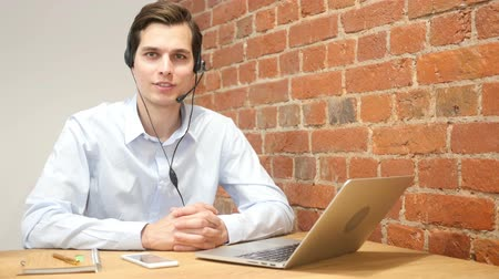 representante : Smiling assistant using a headset in a call center , online customer service