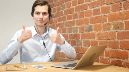 representante : Young modern businessman excited with his success giving thumbs up  ,call center Vídeos