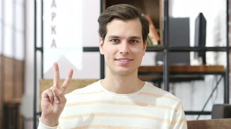 zisky : Young man showing victory sign , success in investment