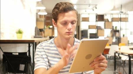 concentrando : Young Man Using Applications on Tablet Computer, Portrait